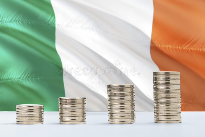 Ireland flag waving in the background with rows of coins for finance and business concept. Saving money royalty free stock photos