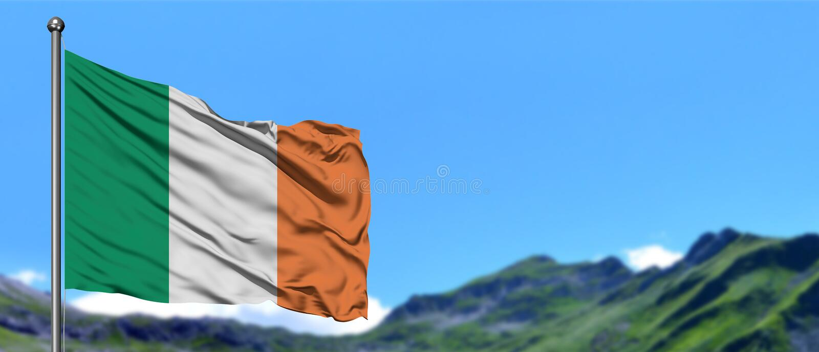 Ireland flag waving in the blue sky with green fields at mountain peak background. Nature theme stock photo