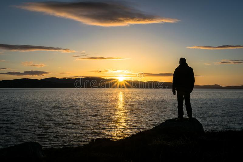 Ireland Sunset View. This is a silhouette of a person watching the sun go down behind some mountatins at the sea. This photo was taken near Buncrana Ireland royalty free stock photos
