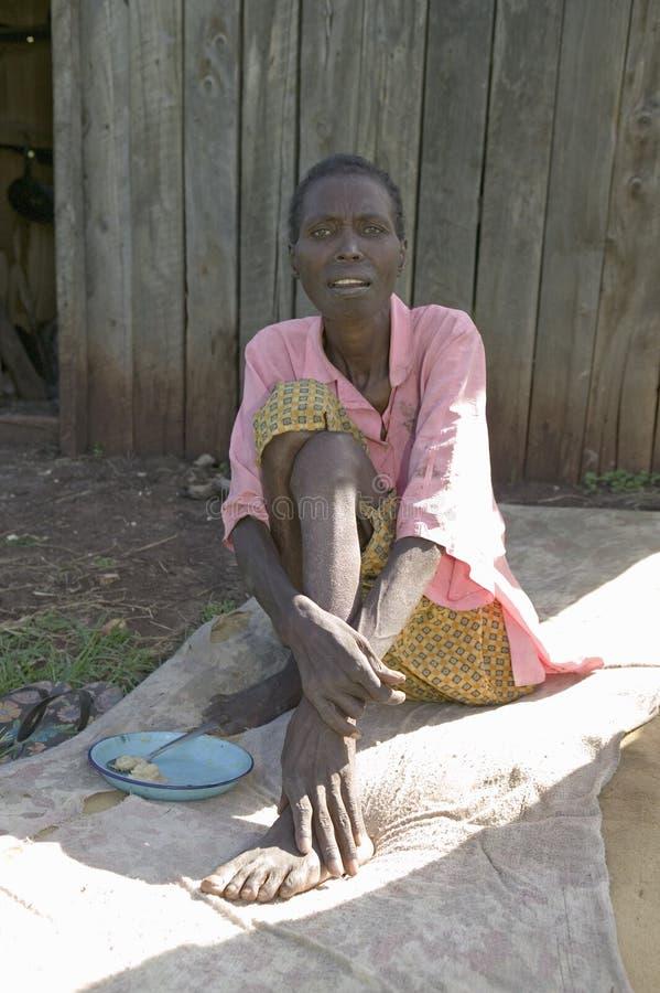 Irene, infekujący z HIV/AIDS, siedzi na ziemi przy Pepo losem angeles Tumaini Jangwani, HIV/AIDS społeczności program rehabilitac zdjęcia stock