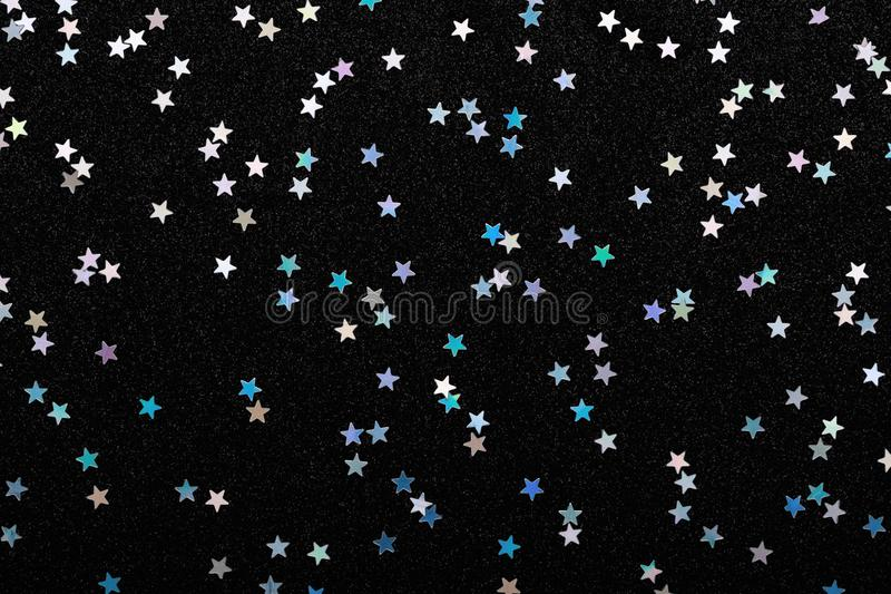 Iridescent Silver stars confetti on black Festive holiday background Glowing sparkles. Iridescent Silver stars confetti on black. Festive holiday background royalty free stock image