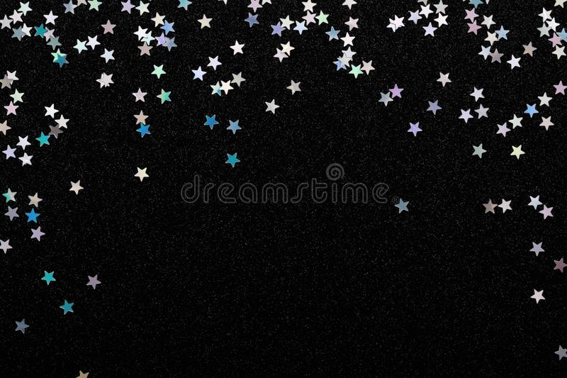 Iridescent Silver stars confetti on black festive background Glowing sparkles frame. Iridescent Silver stars confetti on black Festive holiday background stock images