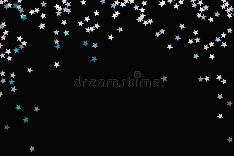 Iridescent Silver stars confetti isolated on black festive background Glowing sparkles frame. Iridescent Silver stars confetti isolated on black. Festive holiday stock photo