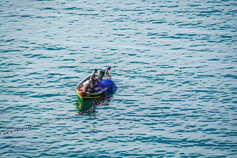 Iris de Cala, Marruecos - 18 de octubre de 2013 Pescadores en el barco usando red cerca de la bahía en la costa marroquí del mar  imagen de archivo libre de regalías