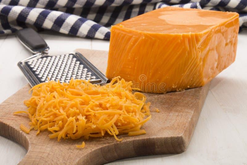 Irisch reifen Sie zerriebenen Cheddar-Käse auf einem hölzernen Brett stockfotografie