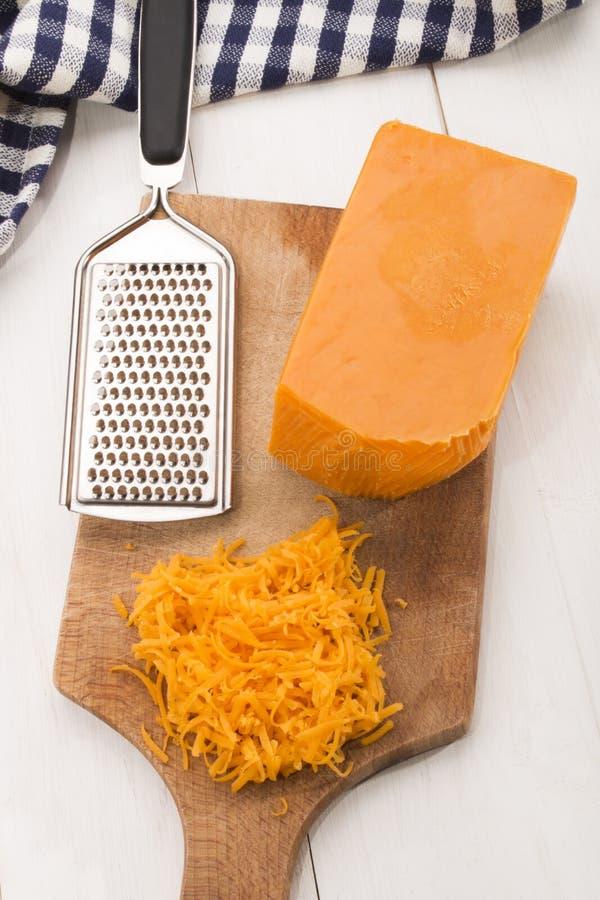 Irisch reifen Sie zerriebenen Cheddar-Käse auf einem hölzernen Brett stockfoto