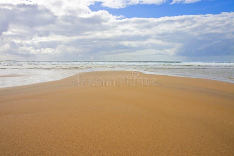Irischer Strand mit Sand und bewölktem Himmel Irland lizenzfreie stockbilder