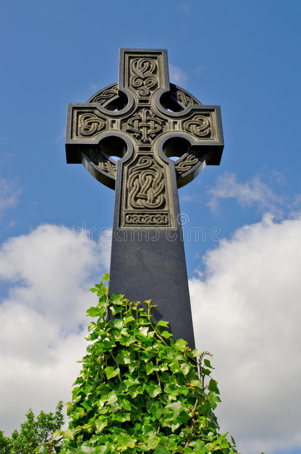 Irish celtic cross with celtic designs. Example of pre 1900 irish celtic cross with traditional celtic carving detail and ivy from a grave in the famous landmark stock photography