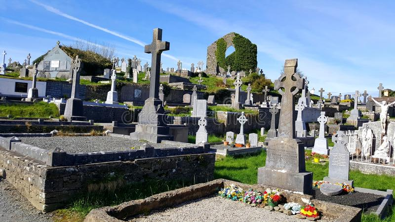 Irish cemetery with ruins of church in background royalty free stock photo