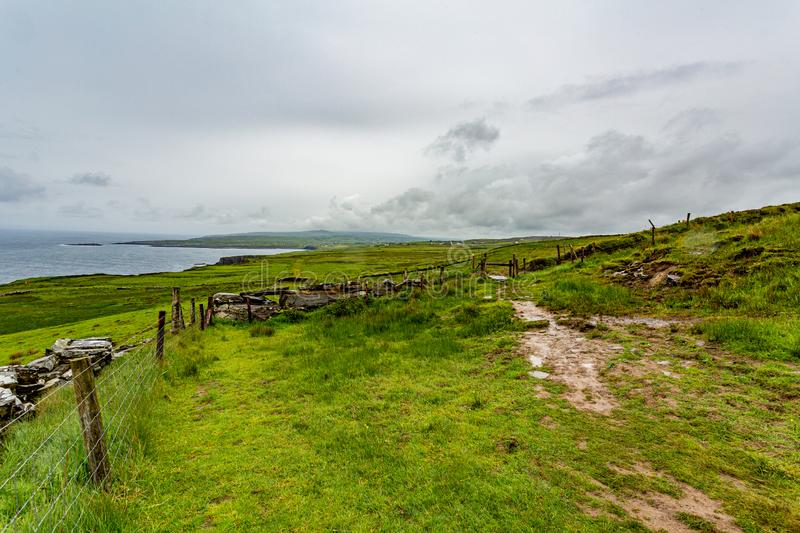 Irish countryside with a rural path between fences in of the coastal route walk. From Doolin to the Cliffs of Moher, geosites and geopark, Wild Atlantic Way royalty free stock images