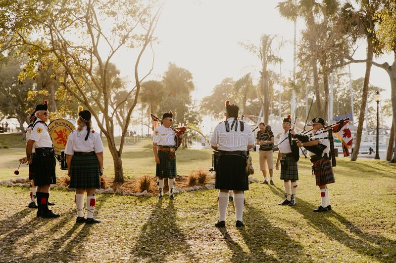 Irish Group of Bagpipe and Drummer Musicians Wearing Authentic European Kilts While Performing Traditional Celtic Music. In Scotland stock photo