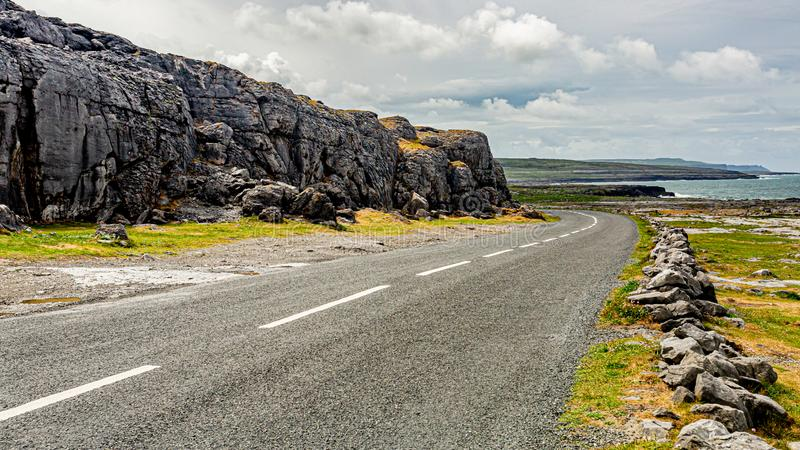 Irish landscape along ​​the Burren with the rural coastal R477 road and the sea in the background. Geosite and geopark, Wild Atlantic Way, cloudy stock image