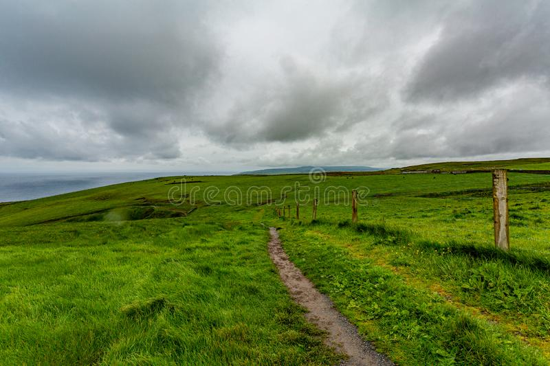 Irish landscape of the spectacular coastal route walk from Doolin to the Cliffs of Moher. Geosites and geopark, Wild Atlantic Way, cloudy spring day in county stock photography