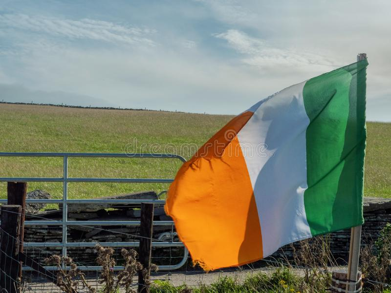 Irish flag by a field. Irish National flag in a field, Green grass field in the background , blue cloudy sky stock photos