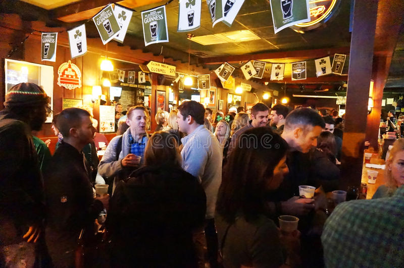 Irish Pub in Washington DC. Photo of people socializing and drinking inside an irish pub called nanny obriens on saint patricks day on 3/17/17 at night. There is stock image