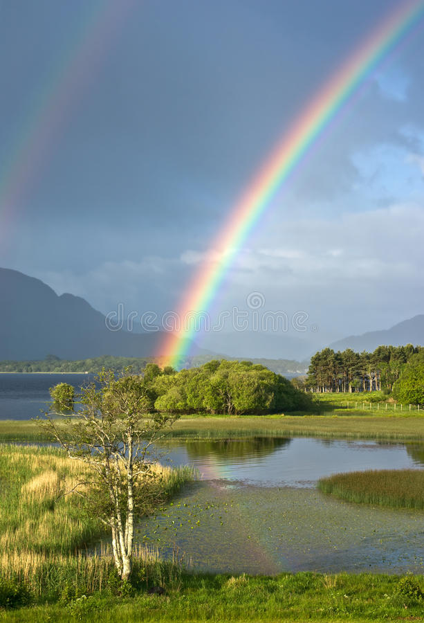 Irish Rainbow. A genuine Irish double rainbow is reflected in the waters of Lough Leane, Killarney, Ireland, with the misty Kerry mountains in the background stock photography