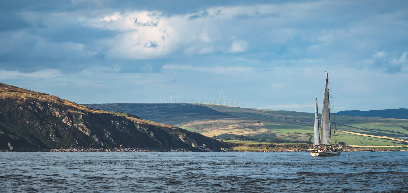 Irish shoreline panorama. Lone sailing yacht. stock photo