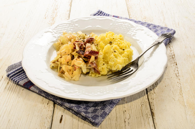 Irish specialty, mashed potato, bacon and cabbage. With fork on a plate stock photos