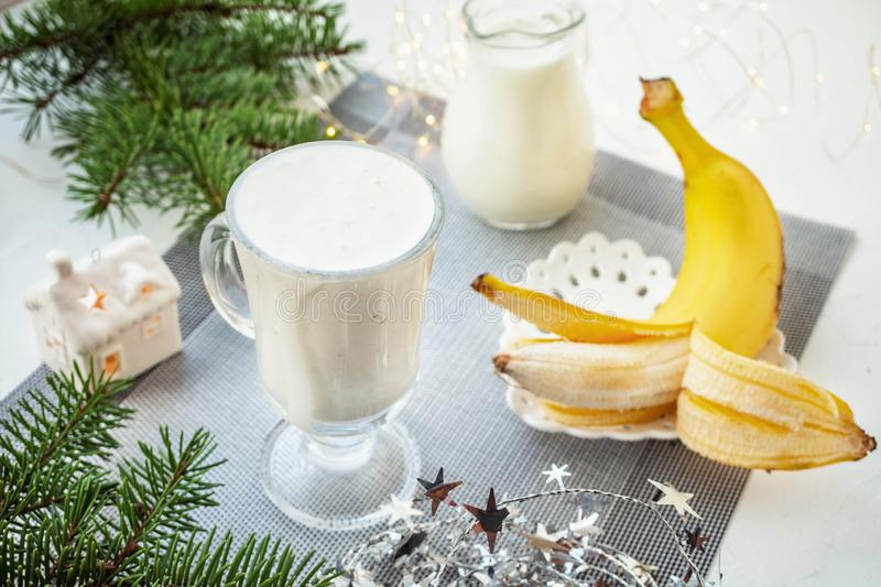 Irish traditional winter cream cocktail eggnog in a glass mug with milk, rum and cinnamon, banana covered with whipped cream, stock images