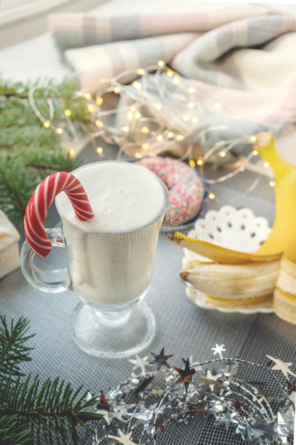 Irish traditional winter cream cocktail eggnog in a glass mug with milk, rum and cinnamon, banana covered with whipped cream, stock image