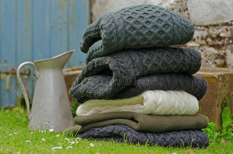 Irish wool Aran knit men's sweaters. Stack of chunky Irish wool cable knit and Aran winter sweaters in fall and winter colours in a pretty Irish rural setting stock photos