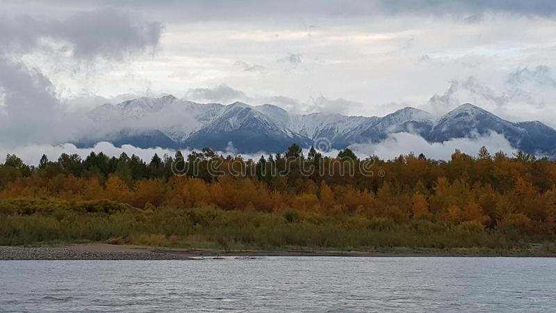 Irkut River in autumn in Siberia. The Irkut River in the autumn in the Tunkinsky valley of the Siberian region of Russia. In the background there are beautiful royalty free stock photo