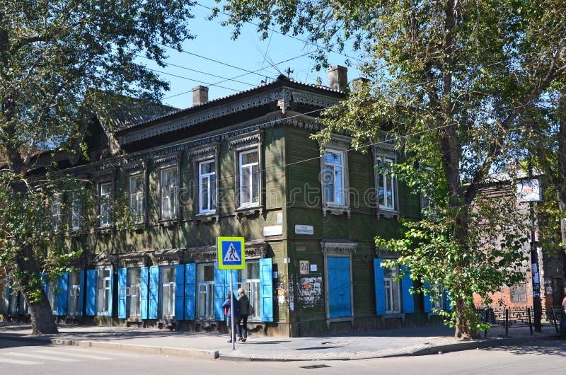 Irkutsk, Rússia, agosto, 29, 2017 Povos que andam perto do número da casa de madeira velho 24 na interseção da rua de Bogdan Khme foto de stock