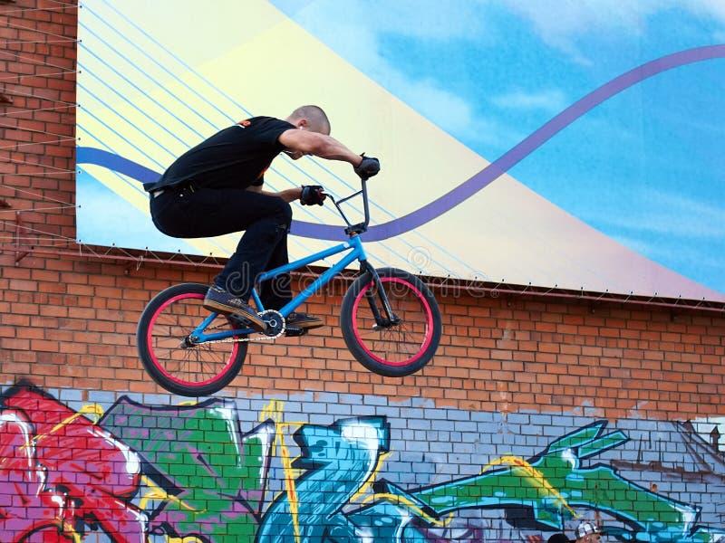 Irkutsk, Rússia - em julho de 2011: o homem executa o bmx do conluio da bicicleta imagem de stock