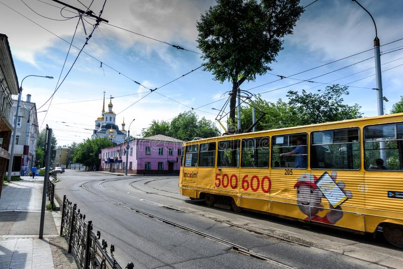 Irkutsk, Rússia, julho, 6, 2019 Bonde com a propaganda que passa perto de Harlampievskaya Michael a igreja do arcanjo fotos de stock royalty free