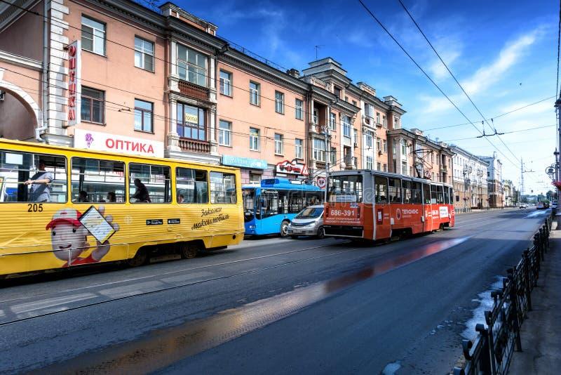 Irkutsk, Rússia, julho, 6, 2019 Bonde e ônibus com a propaganda que passa na rua de Lenin fotografia de stock