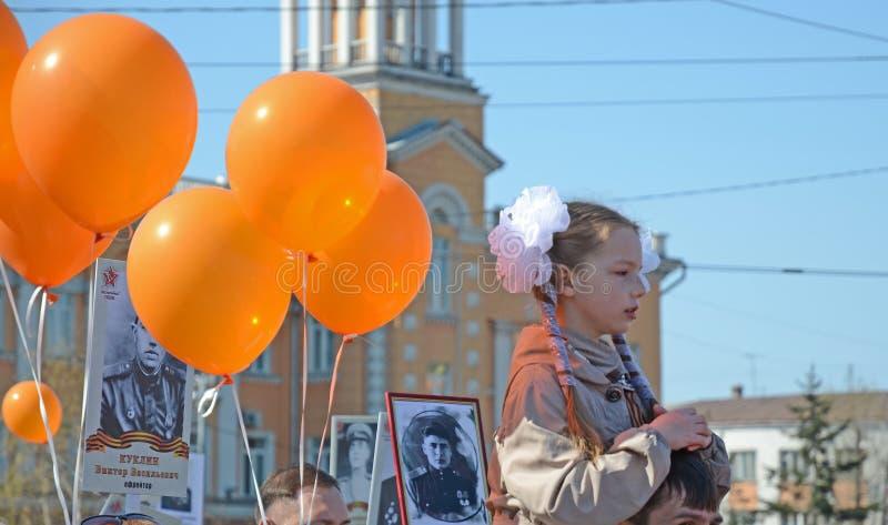 Irkutsk Rosja, Maj, - 9, 2015: Młoda dziewczyna na ojcach brać na swoje barki i pomarańcze szybko się zwiększać na zwycięstwo dni obrazy stock