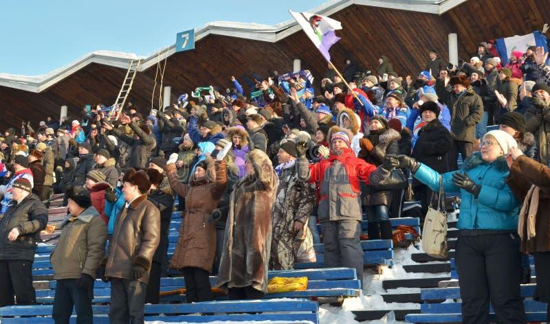 Irkutsk, Rusia - febrero, 23 2012: Fans jubilosas y una bandera en los soportes durante el partido bandy imagen de archivo libre de regalías