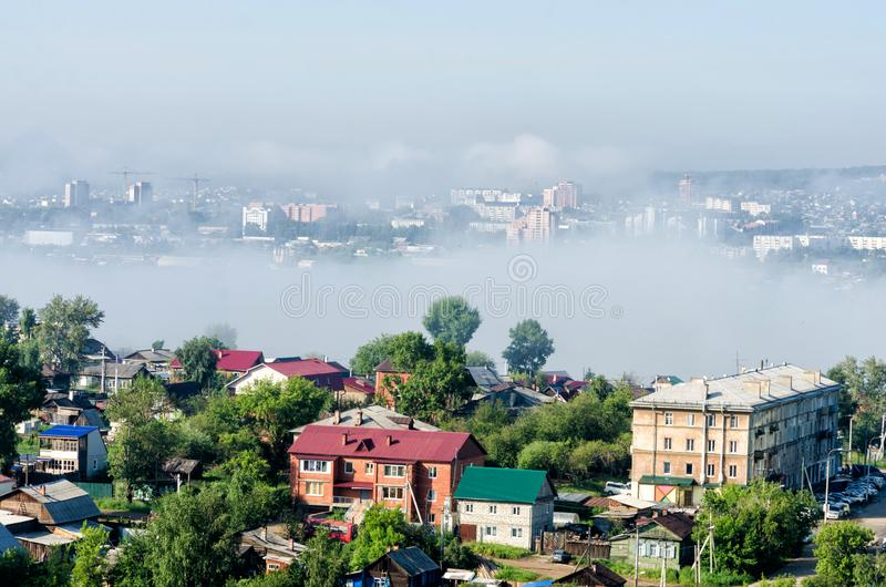 IRKUTSK, RUSSIA - July 8, 2013: Panoramic top view the city of Irkutsk on sunny summer day with fog royalty free stock photo