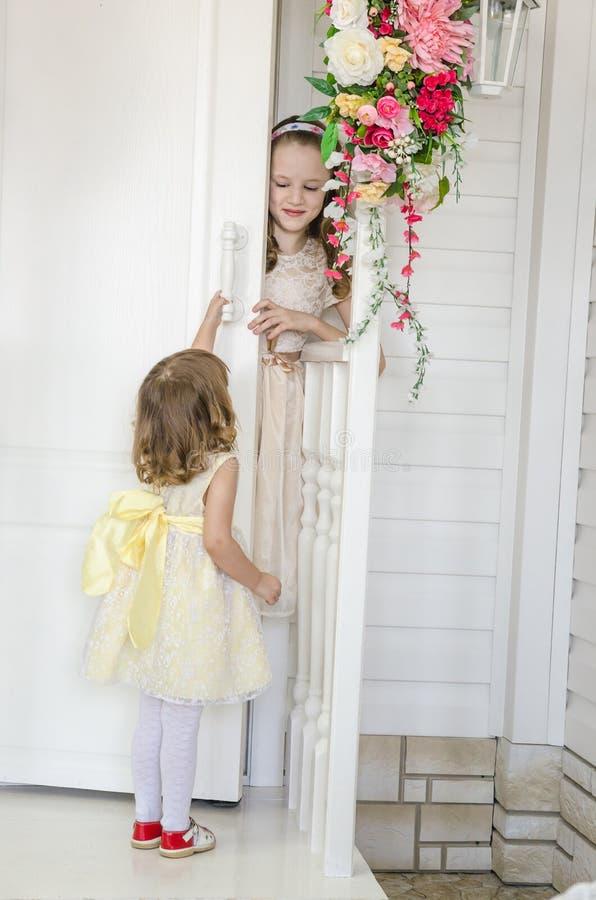 Irkutsk, Russland - Februar 2017 öffnet kleines nettes Mädchen die Tür mit Blumen und Mädchen schaut heraus um die Tür stockfoto