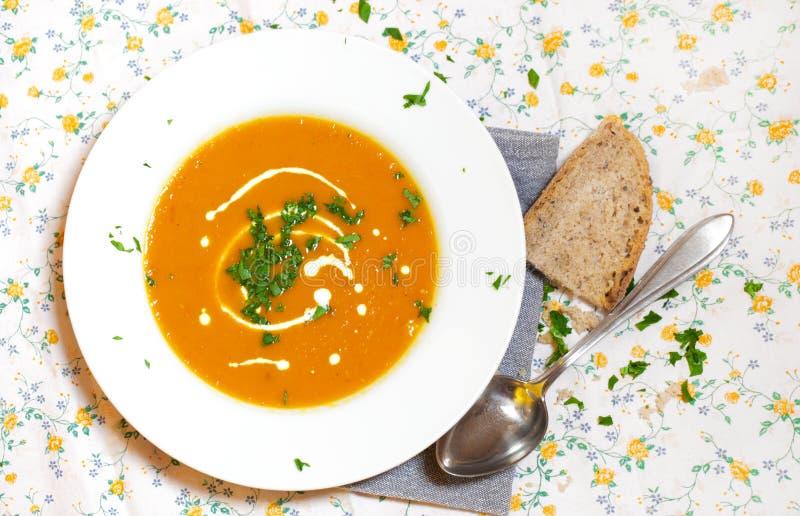 Morotsoup med kräm och parsley, brödskiva arkivfoton