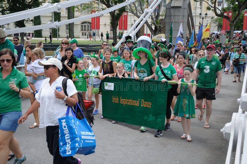 Irländska inspirerande dansgruppparaders som korsar den Cavengah bron i Singapore under dagen 2018 för St Patrick ` s royaltyfri bild