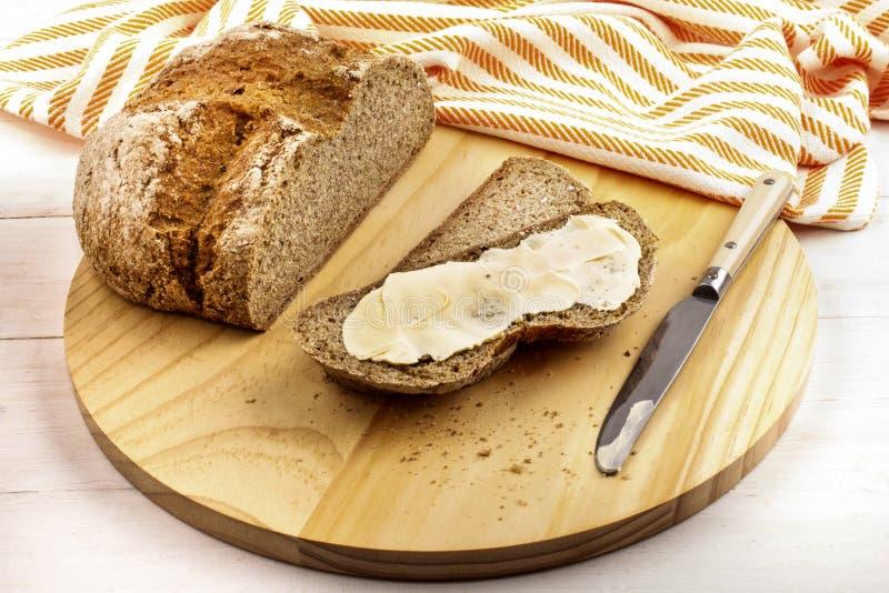Irländskt sodavattenbröd med krämigt irländskt smör på en träplatta arkivfoto