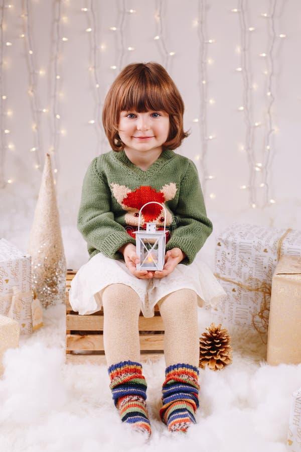 IRL con los ojos azules que se sientan con la vela ligera mirando in camera la Navidad de celebración imagen de archivo