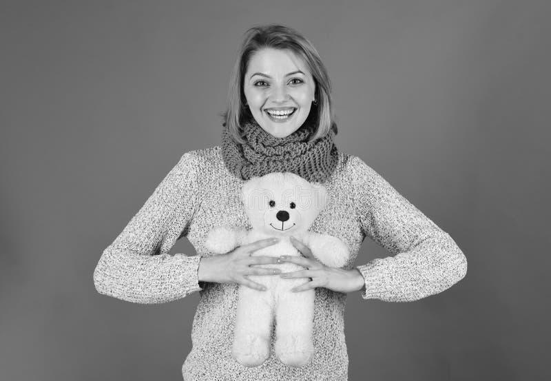 Irl med den lyckliga framsidan spelar med den vita mjuka leksaken Nätt leksakbegrepp Dam med omfamningar för blont hår med björne royaltyfria foton