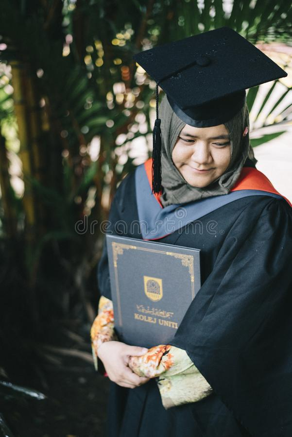 A IRL que guarda um grau certificate da faculdade de UNITI no dia de graduação foto de stock royalty free