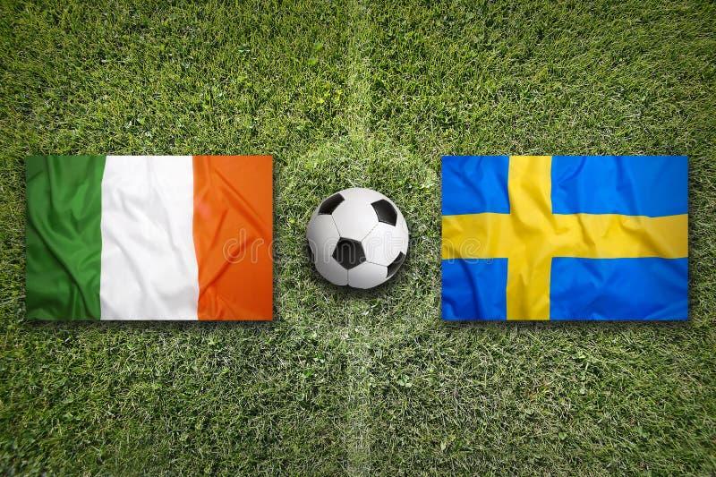 Irland vs Sverige flaggor på fotbollfält royaltyfri fotografi