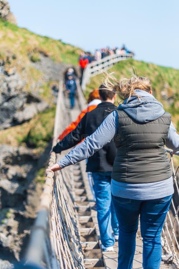 IRLANDA DO NORTE, REINO UNIDO - 8 DE ABRIL DE 2019: Os turistas assustados cruzam a ponte de corda perigosa mas bonita de Carrick fotos de stock royalty free