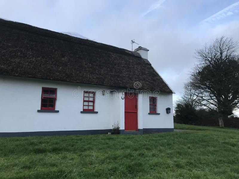 Irlandzka chałupa z pokrywającym strzechą dachowym i czerwonym drzwi zdjęcie royalty free