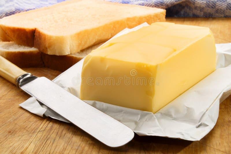 Irlandzki masło z świeżym pokrojonym chlebem na drewnianej desce obrazy stock