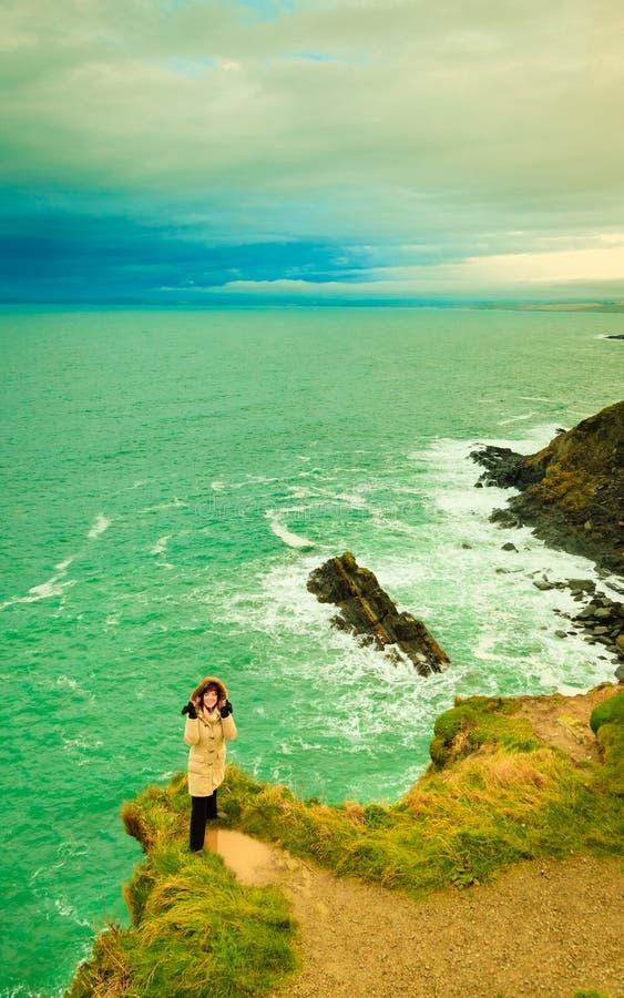 Irlandzkiej atlantyckiej brzegowej kobiety turystyczna pozycja na rockowej falezie fotografia royalty free