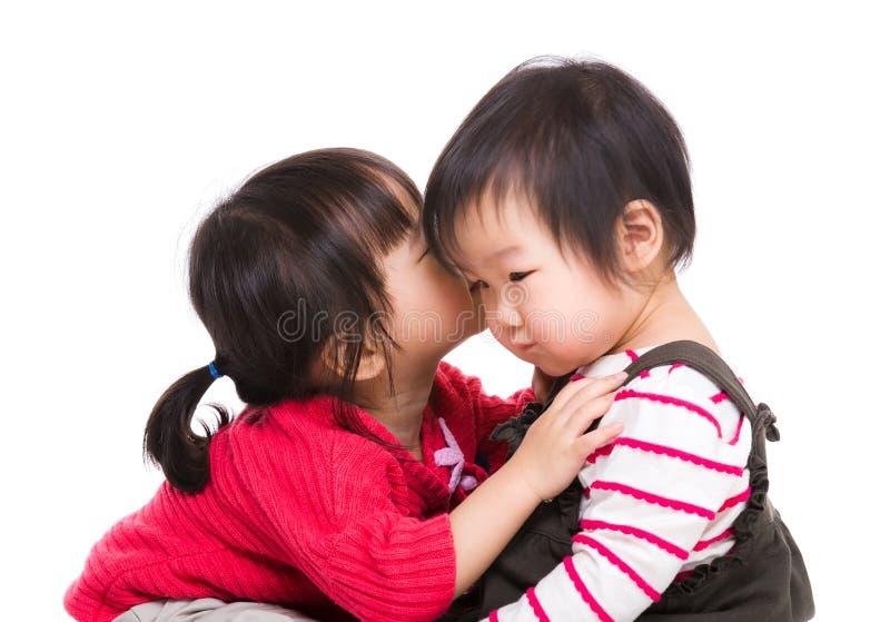 A irmã asiática beija sua irmã da maca imagens de stock royalty free