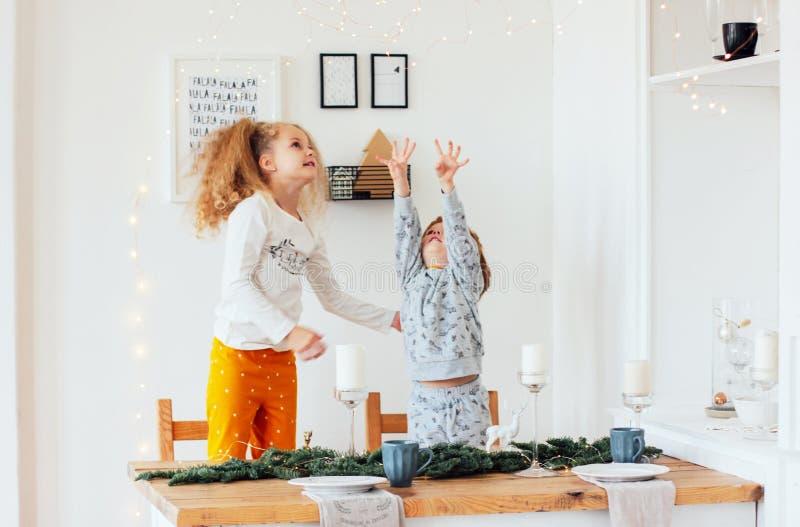 Irmã bonito e irmão nos pijamas na tabela festiva, Escandinávia imagens de stock royalty free