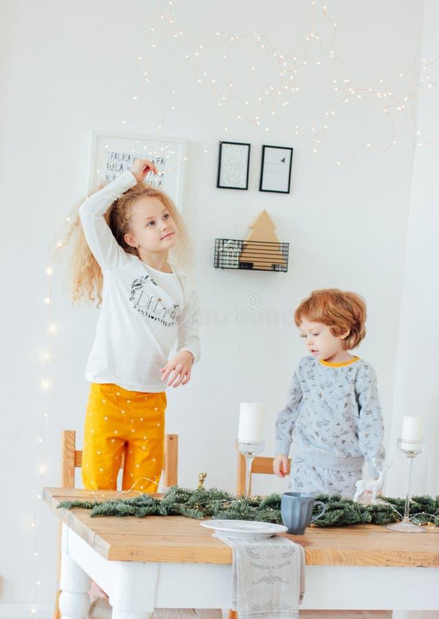 Irmã bonito e irmão nos pijamas na tabela festiva, Escandinávia imagem de stock royalty free