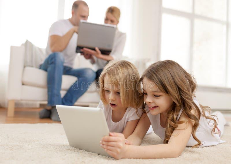 Irmã de sorriso com PC e pais da tabuleta sobre para trás imagens de stock royalty free