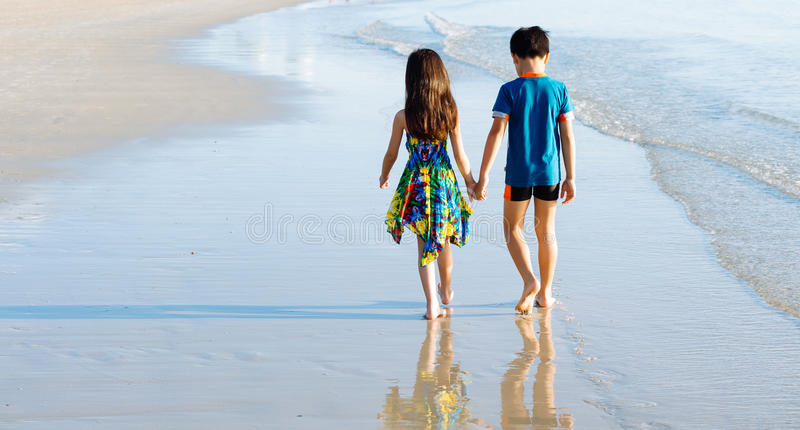 Irmã do irmão que guarda a caminhada da mão na praia foto de stock